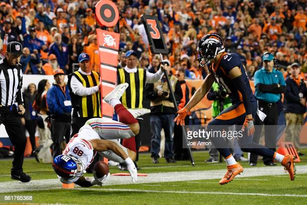Evan Engram of the New York Giants scores a touchdown as Justin Simmons of the Denver Broncos defends during the second quarter of the on Sunday...