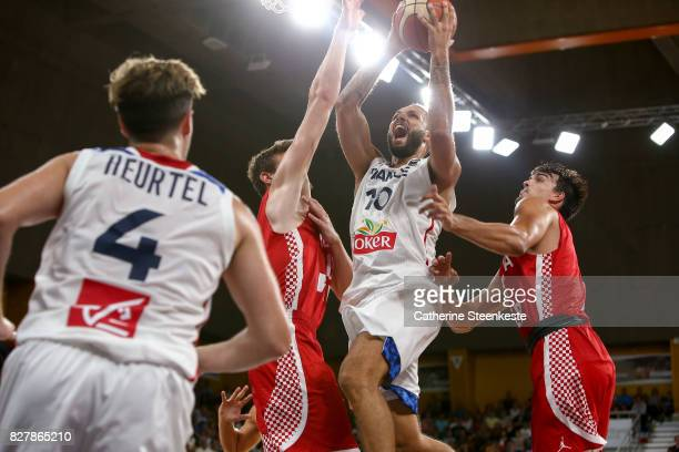 Evan Fournier of France is at the basket against Dragan Bender and Dario Saric of Croatia during the international friendly game between France v...