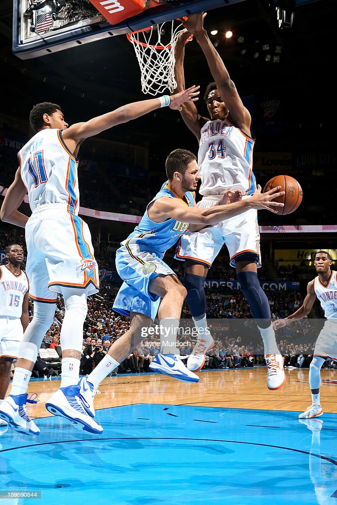 Evan Fournier #94 of the Denver Nuggets passes the ball in the lane against Hasheem Thabeet #34 and Jeremy Lamb #11 of the Oklahoma City Thunder on January 16, 2013 at the Chesapeake Energy Arena in Oklahoma City, Oklahoma.