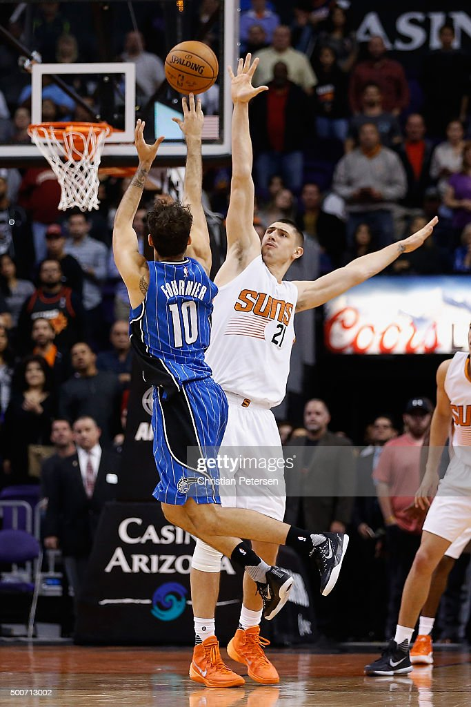 Evan Fournier #10 of the Orlando Magic attempts a last second shot over Alex Len #21 of the Phoenix Suns during the NBA game at Talking Stick Resort Arena on December 9, 2015 in Phoenix, Arizona. The Suns defeated the Magic 107-104.