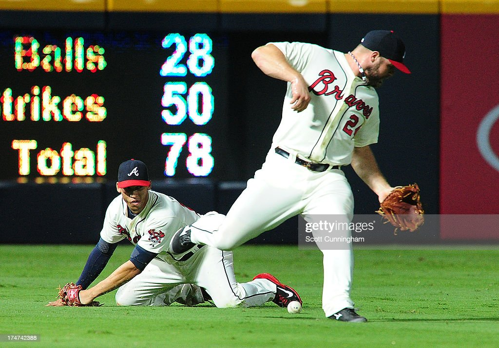 <a gi-track='captionPersonalityLinkClicked' href=/galleries/search?phrase=Evan+Gattis&family=editorial&specificpeople=8977937 ng-click='$event.stopPropagation()'>Evan Gattis</a> #24 (R) and <a gi-track='captionPersonalityLinkClicked' href=/galleries/search?phrase=Andrelton+Simmons&family=editorial&specificpeople=8978424 ng-click='$event.stopPropagation()'>Andrelton Simmons</a> #19 of the Atlanta Braves are unable to make a catch of a run scoring single by Carlos Beltran #3 of the St. Louis Cardinals (not pictured) at Turner Field on July 28, 2013 in Atlanta, Georgia.