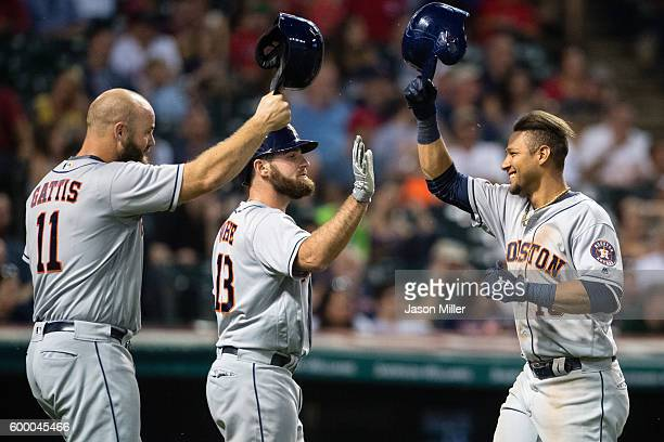 Evan Gattis and Tyler White celebrate with Yulieski Gurriel of the Houston Astros after Gurriel hitt a two run home run during the eighth inning...