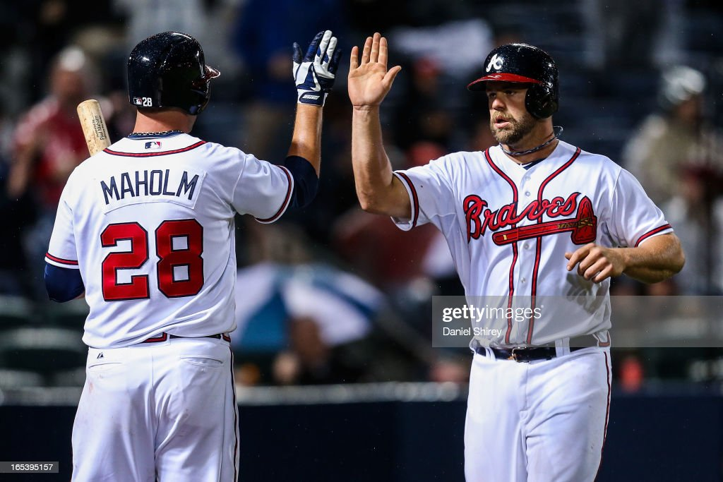 Evan Gattis #24 celebrates his solo home run with <a gi-track='captionPersonalityLinkClicked' href=/galleries/search?phrase=Paul+Maholm&family=editorial&specificpeople=585406 ng-click='$event.stopPropagation()'>Paul Maholm</a> #28 of the Atlanta Braves in the fourth inning of the game against the Philadelphia Phillies at Turner Field on April 3, 2013 in Atlanta, Georgia.