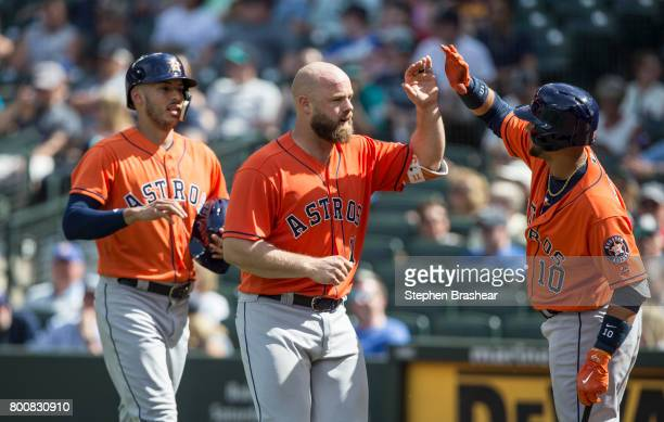 Evan Gattis center of the Houston Astros is congratulated by Yuli Gurriel of the Houston Astros after hitting a tworun home run off of relief pitcher...