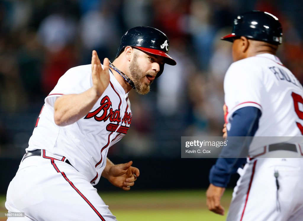 Evan Gattis #24 of the Atlanta Braves celebrates his solo homer in the bottom of the ninth that tied the game 4-4 against the Minnesota Twins with first base coach Terry Pendleton #9 at Turner Field on May 21, 2013 in Atlanta, Georgia.
