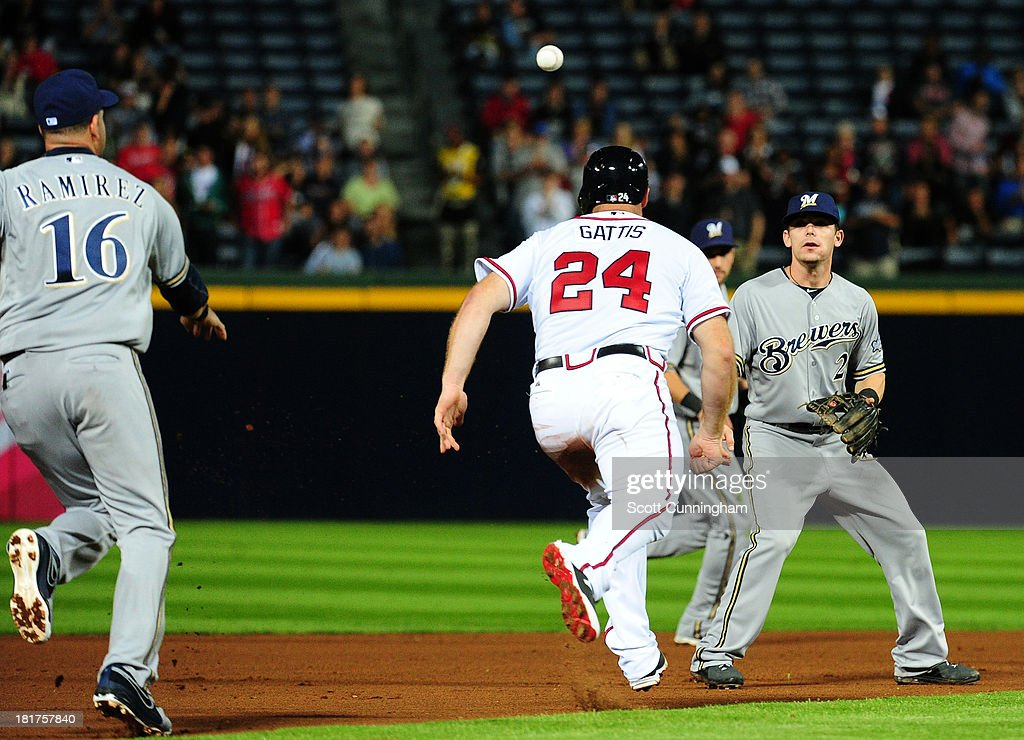 <a gi-track='captionPersonalityLinkClicked' href=/galleries/search?phrase=Evan+Gattis&family=editorial&specificpeople=8977937 ng-click='$event.stopPropagation()'>Evan Gattis</a> #24 of the Atlanta Braves gets caught in a rundown against <a gi-track='captionPersonalityLinkClicked' href=/galleries/search?phrase=Aramis+Ramirez&family=editorial&specificpeople=239509 ng-click='$event.stopPropagation()'>Aramis Ramirez</a> #16 and <a gi-track='captionPersonalityLinkClicked' href=/galleries/search?phrase=Scooter+Gennett&family=editorial&specificpeople=5502894 ng-click='$event.stopPropagation()'>Scooter Gennett</a> #2 of the Milwaukee Brewers at Turner Field on September 24, 2013 in Atlanta, Georgia.
