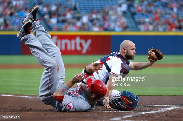 Evan Gattis of the Atlanta Braves holds up his glove after tagging out Joey Votto of the Cincinnati Reds at the plate to end the first inning at...