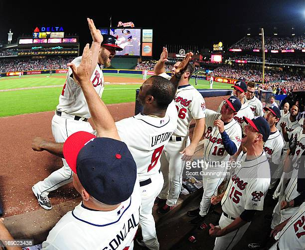 Evan Gattis of the Atlanta Braves is congratulated by teammates after hitting an eighth inning pinch hit home run against the Los Angeles Dodgers at...