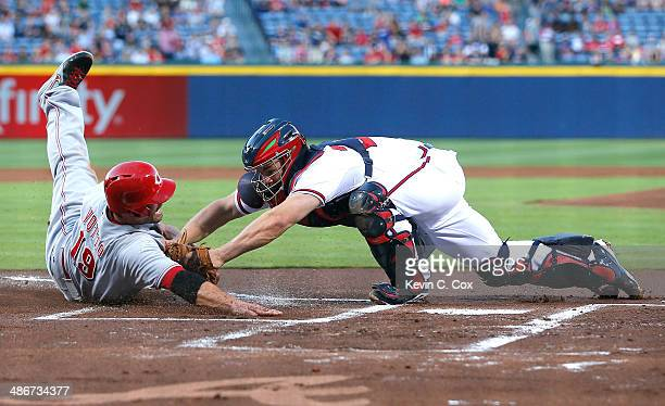 Evan Gattis of the Atlanta Braves tags out Joey Votto of the Cincinnati Reds at the plate to end the first inning at Turner Field on April 25 2014 in...
