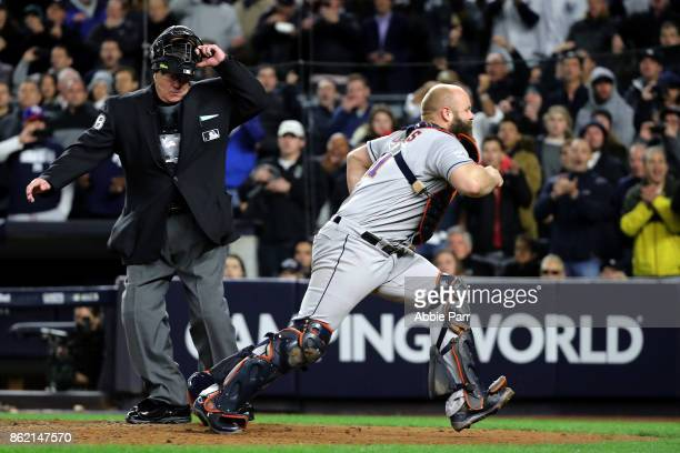 Evan Gattis of the Houston Astros chases a passed ball scoring a run for the New York Yankees during the fourth inning in Game Three of the American...