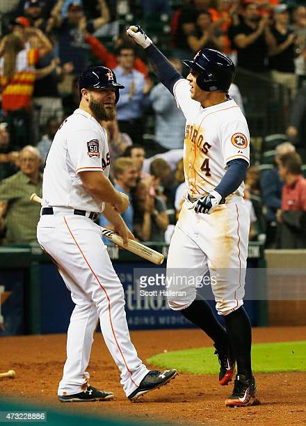 Evan Gattis of the Houston Astros greets teammate George Springer after Springer hit a solo home run in the eighth inning of their game against the...