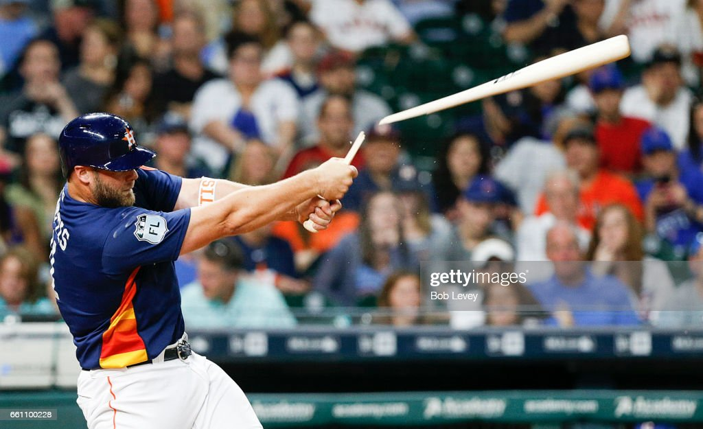 Evan Gattis #11 of the Houston Astros hits a broken bat double in the sixth inning against the Chicago Cubs during an exhibition game at Minute Maid Park on March 30, 2017 in Houston, Texas.