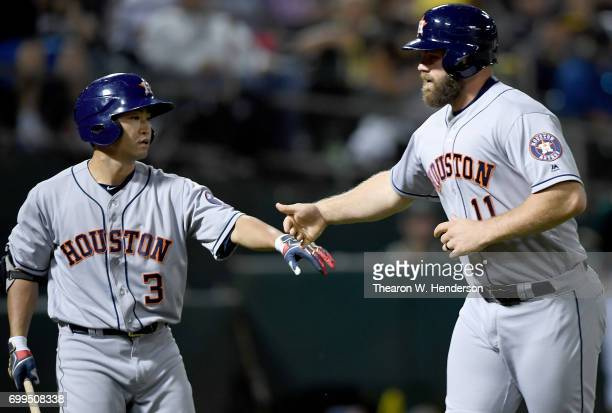 Evan Gattis of the Houston Astros is congratulated by Norichika Aoki after Gattis scored against the Oakland Athletics in the top of the six inning...