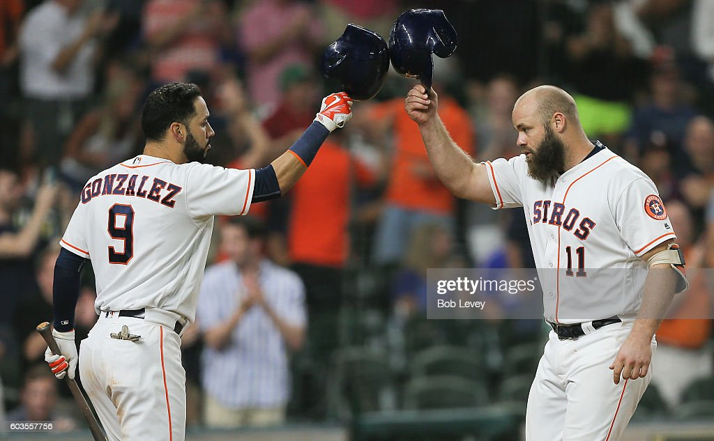 Evan Gattis #11 of the Houston Astros taps helmets with Marwin Gonzalez #9 after hitting a home run in the ninth inning against the Texas Rangers at Minute Maid Park on September 12, 2016 in Houston, Texas.