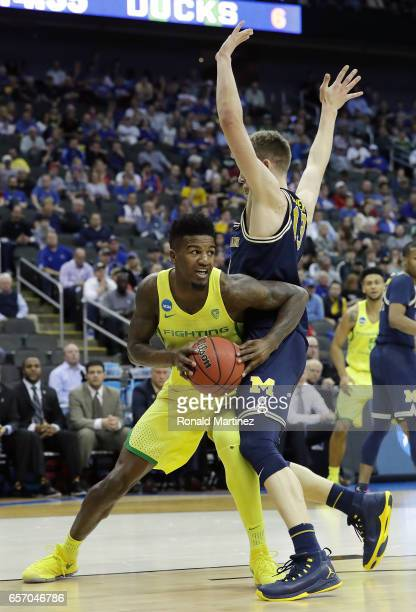 Evan Gross of the Oregon Ducks is defended by Moritz Wagner of the Michigan Wolverines during the 2017 NCAA Men's Basketball Tournament Midwest...