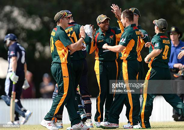 Evan Gulbis and Clive Rose of Tasmania celebrate with fellow team mates after taking the wicket of Alex Keath of Victoria during the Matador BBQs One...