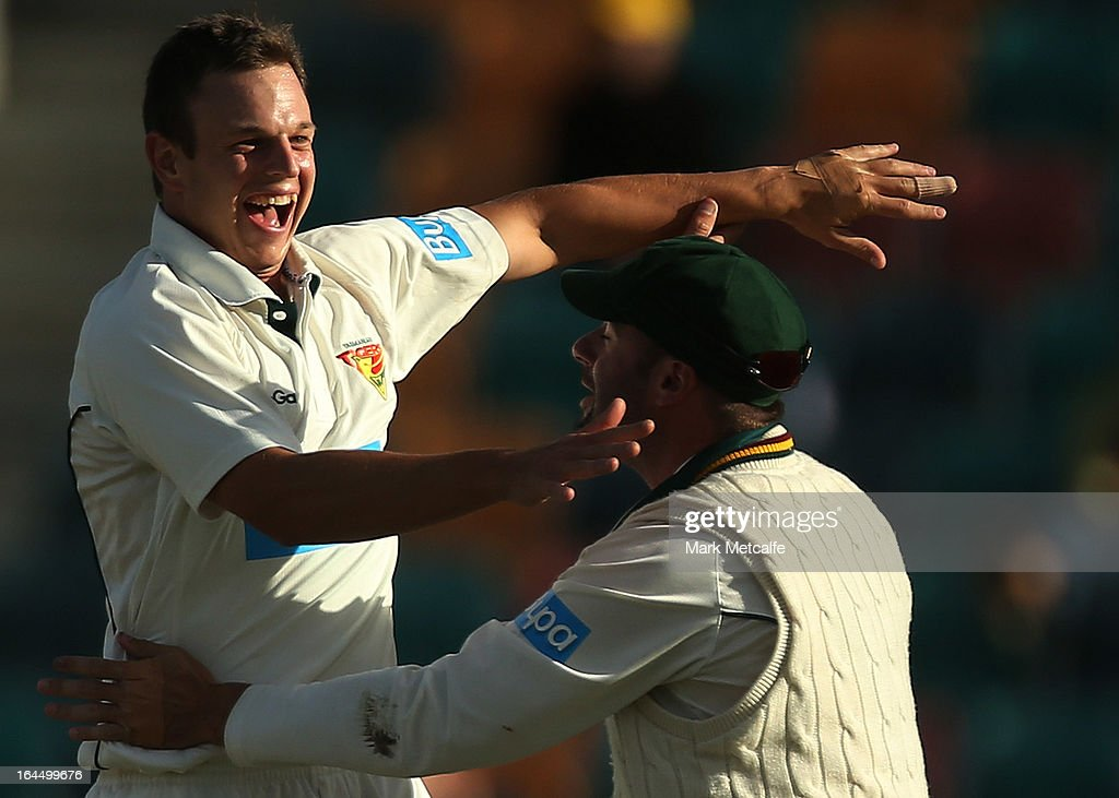 Evan Gulbis of the Tigers celebrates with teammate Alex Doolan after taking the wicket of Peter Forrest of the Bulls during day three of the Sheffield Shield final between the Tasmania Tigers and the Queensland Bulls at Blundstone Arena on March 24, 2013 in Hobart, Australia.