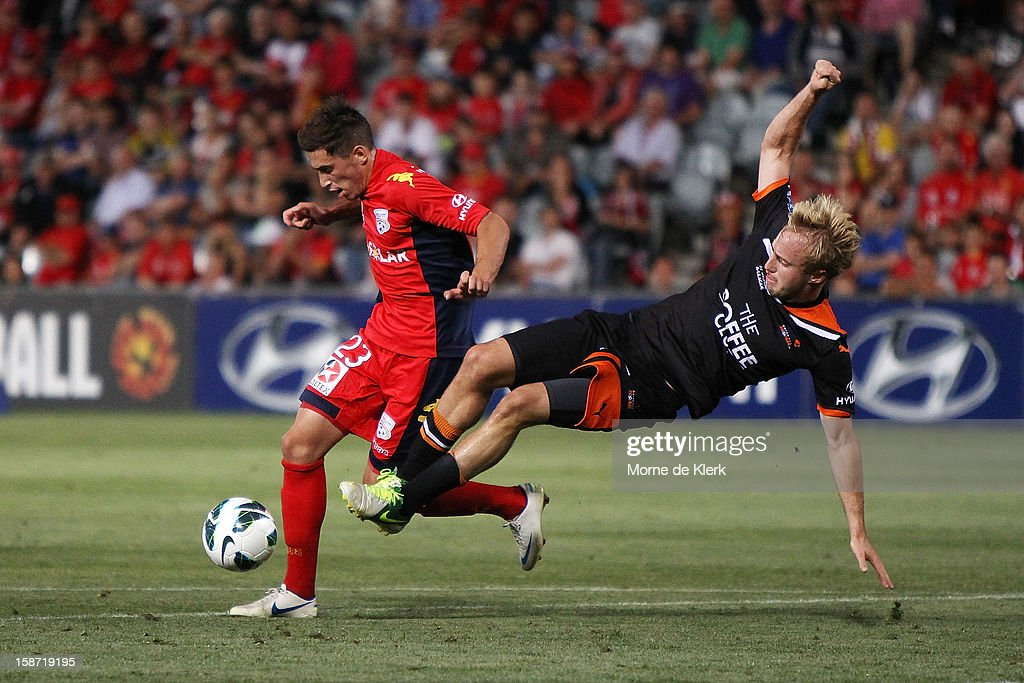Evan Kostopoulos of Adelaide is tackled by Mitchell Nichols of Brisbane during the round 13 A-League match between Adelaide United and the Brisbane Roar at Hindmarsh Stadium on December 26, 2012 in Adelaide, Australia.