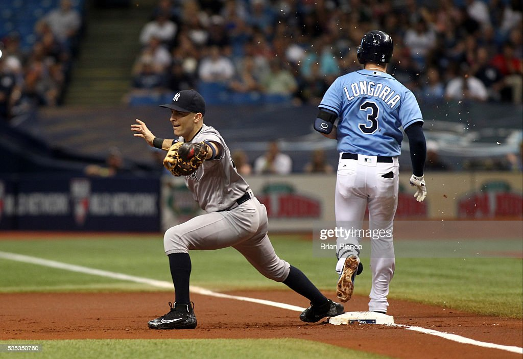 <a gi-track='captionPersonalityLinkClicked' href=/galleries/search?phrase=Evan+Longoria&family=editorial&specificpeople=2349329 ng-click='$event.stopPropagation()'>Evan Longoria</a> #3 of the Tampa Bay Rays beats first baseman <a gi-track='captionPersonalityLinkClicked' href=/galleries/search?phrase=Dustin+Ackley&family=editorial&specificpeople=4352278 ng-click='$event.stopPropagation()'>Dustin Ackley</a> #29 of the New York Yankees to first base on his fielder's choice during the first inning of a game on May 29, 2016 at Tropicana Field in St. Petersburg, Florida.