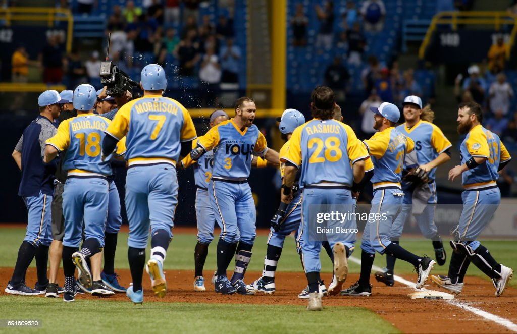 Evan Longoria #3 of the Tampa Bay Rays, center, is surrounded by teammates after hitting a walk off RBI single to score Peter Bourjos during the 10th inning of game one of a double header against the Oakland Athletics on June 10, 2017 at Tropicana Field in St. Petersburg, Florida.