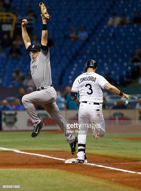 Evan Longoria of the Tampa Bay Rays reaches first base ahead of first baseman Mark Teixeira of the New York Yankees on an infield single to third...