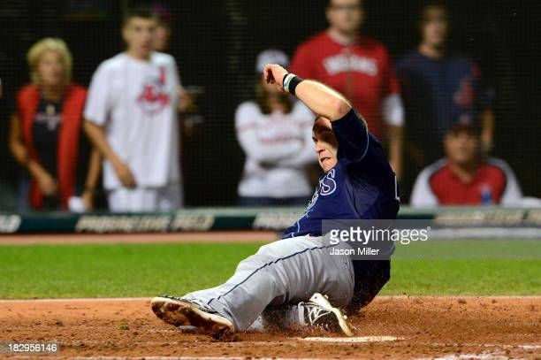 Evan Longoria of the Tampa Bay Rays slides to home to score after Desmond Jennings of the Tampa Bay Rays hit an RBI double to left field against...