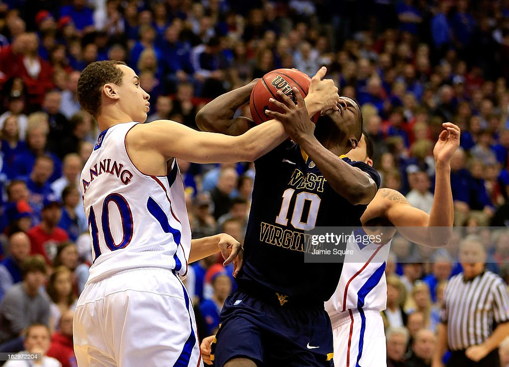 Evan Manning #10 of the Kansas Jayhawks fouls Eron Harris #10 of the West Virginia Mountaineers during the game at Allen Fieldhouse on March 2, 2013 in Lawrence, Kansas.