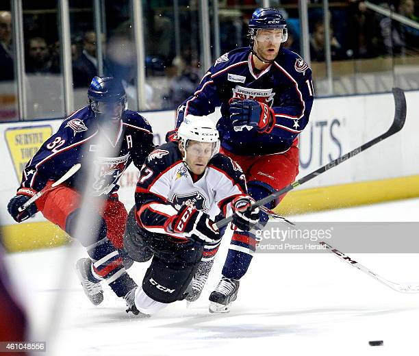 Evan Oberg of the Portland Pirates dives to try and keep the puck away from Springfield Falcon players Frederic St Denis at left and Mike Hoeffel at...