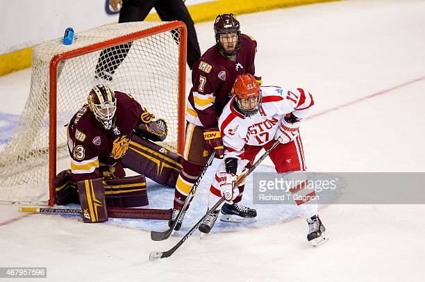 Evan Rodrigues of the Boston University Terriers is checked by Andy Welinski of the Minnesota Duluth Bulldogs during the NCAA Division I Men's Ice...