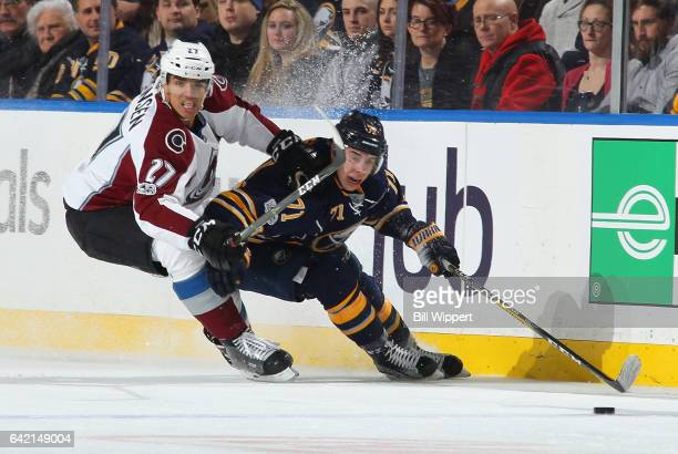 Evan Rodrigues of the Buffalo Sabres controls the puck along the boards against Andreas Martinsen of the Colorado Avalanche during an NHL game at the...