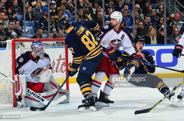 Evan Rodrigues of the Buffalo Sabres is upended by Brandon Dubinsky of the Columbus Blue Jackets as Marcus Foligno is defended by Joonas Korpisalo...