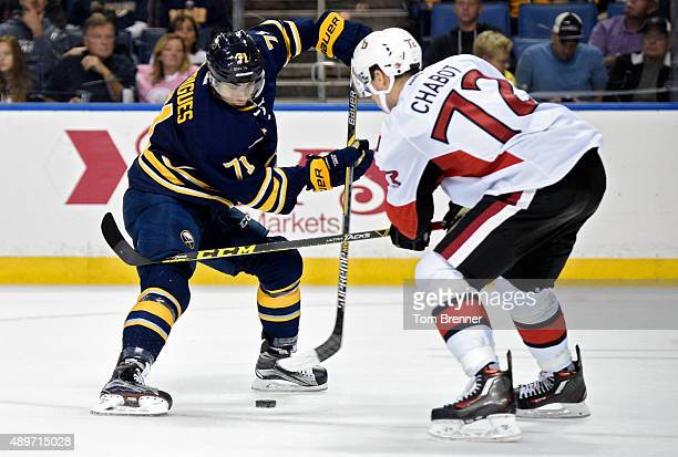 Evan Rodrigues of the Buffalo Sabres moves the puck around Thomas Chabot of the Ottawa Senators at the First Niagara Center on September 23 2015 in...