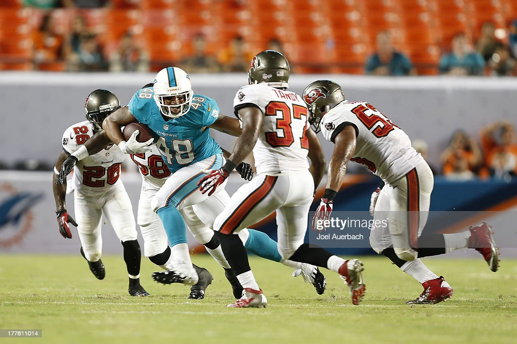 Evan Rodriguez #48 of the Miami Dolphins runs with the ball against the Tampa Bay Buccaneers during a preseason game on August 24, 2013 at Sun Life Stadium in Miami Gardens, Florida. The Buccaneers defeated the Dolphins 17-16.