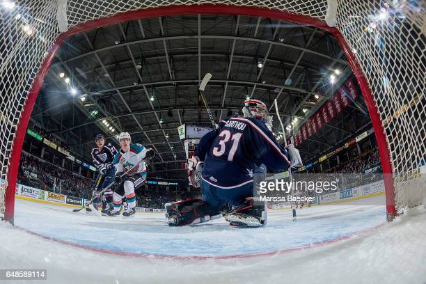 Evan Sarthou of the TriCity Americans defends the net as Kole Lind of the Kelowna Rockets looks for the pass and a shot on net on March 4 2017 at...