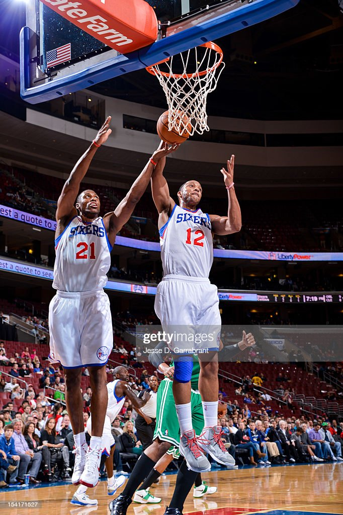 Evan Turner #12 and Thaddeus Young #21 of the Philadelphia 76ers go for a rebound against the Boston Celtics during a pre-season game at the Wells Fargo Center on October 15, 2012 in Philadelphia, Pennsylvania.