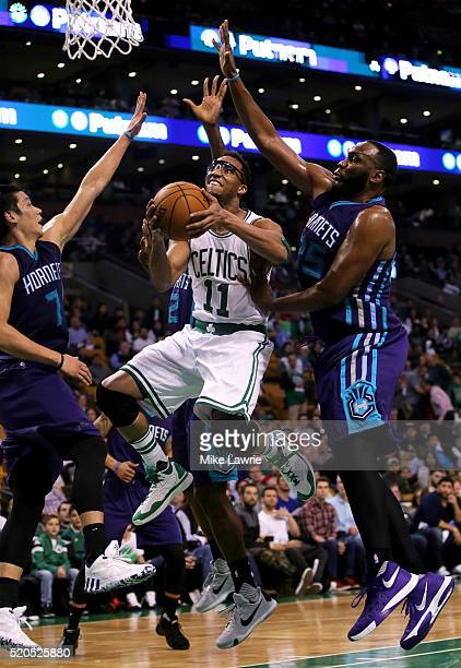 Evan Turner of the Boston Celtics drives to the basket against Jeremy Lin and Al Jefferson of the Charlotte Hornets in the fourth quarter at TD...