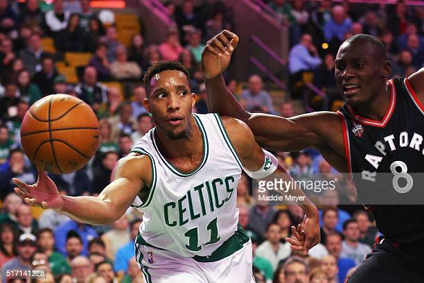 Evan Turner of the Boston Celtics saves a rebound from going out of bounds with pressure from Bismack Biyombo of the Toronto Raptors during the first...