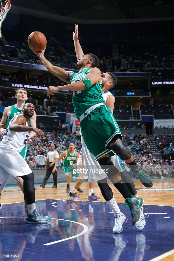 Evan Turner of the Boston Celtics shoots a layup against Jeff Taylor of the Charlotte Hornets at Time Warner Cable Arena on March 30 2015 in...