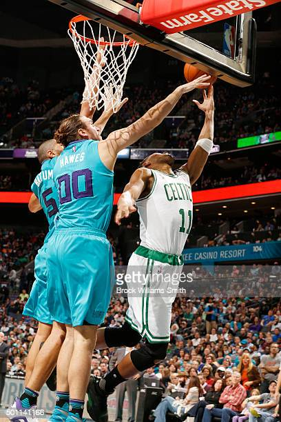 Evan Turner of the Boston Celtics shoots against Spencer Hawes of the Charlotte Hornets during the game at the Time Warner Cable Arena on December 12...