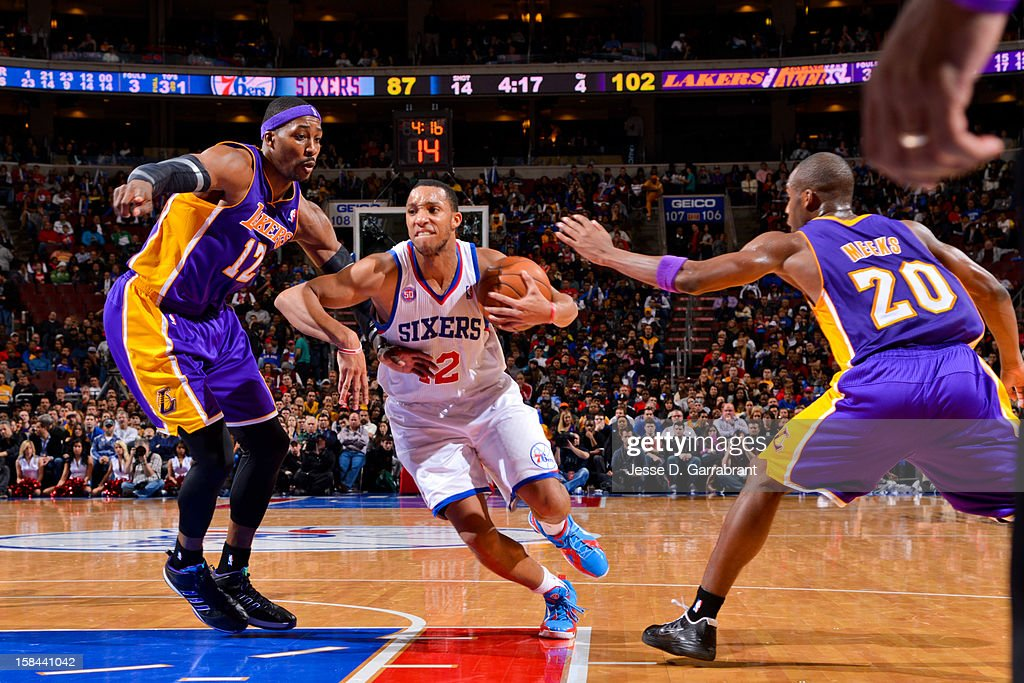 Evan Turner #12 of the Philadelphia 76ers drives to the basket against Dwight Howard #12 and Jodie Meeks #20 of the Los Angeles Lakers at the Wells Fargo Center on December 16, 2012 in Philadelphia, Pennsylvania.