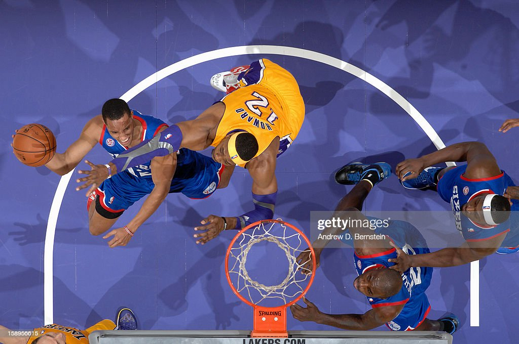 Evan Turner #12 of the Philadelphia 76ers drives to the basket against Dwight Howard #12 of the Los Angeles Lakers at Staples Center on January 1, 2013 in Los Angeles, California.