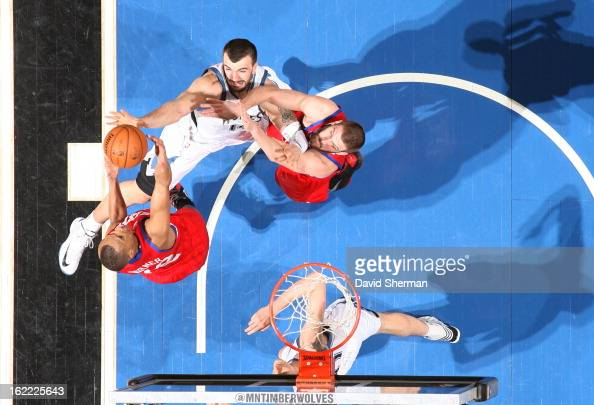 Evan Turner of the Philadelphia 76ers gains the ball control against Nikola Pekovic of the Minnesota Timberwolves during the game between...