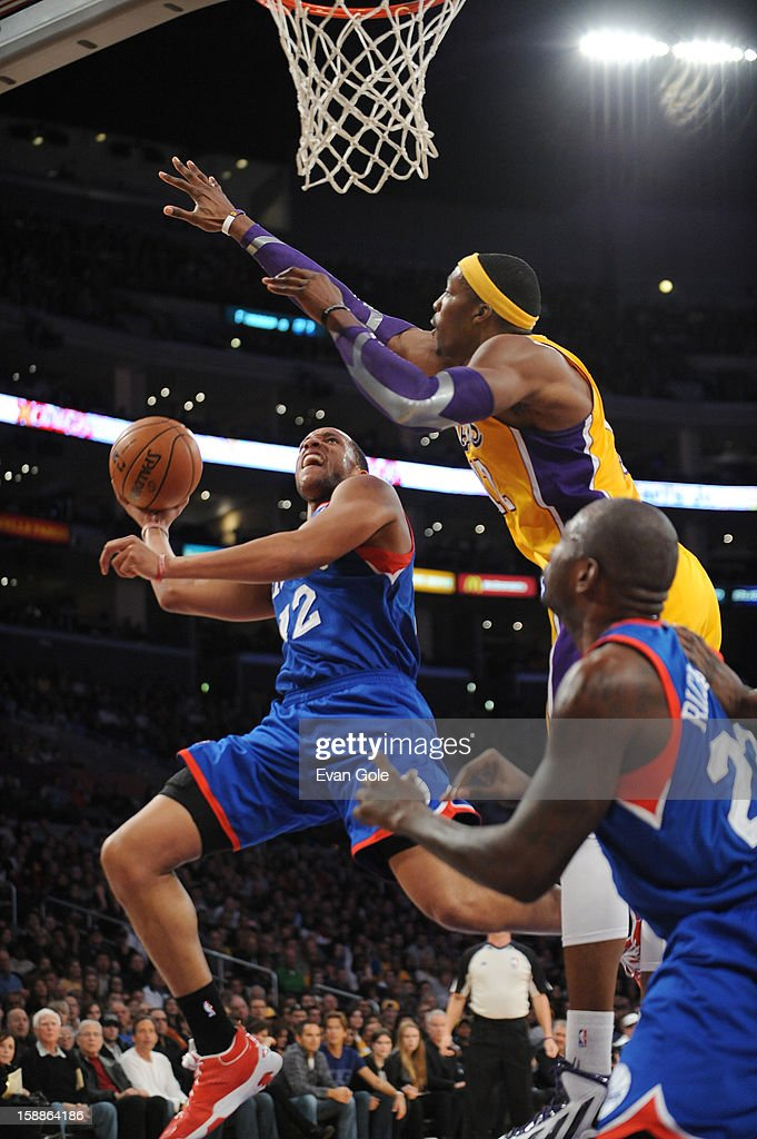 Evan Turner #12 of the Philadelphia 76ers goes to the basket Dwight Howard #12 of the Los Angeles Lakers during the game between the Philadelphia 76ers and the Los Angeles Lakers at Staples Center on January 1, 2013 in Los Angeles, California.