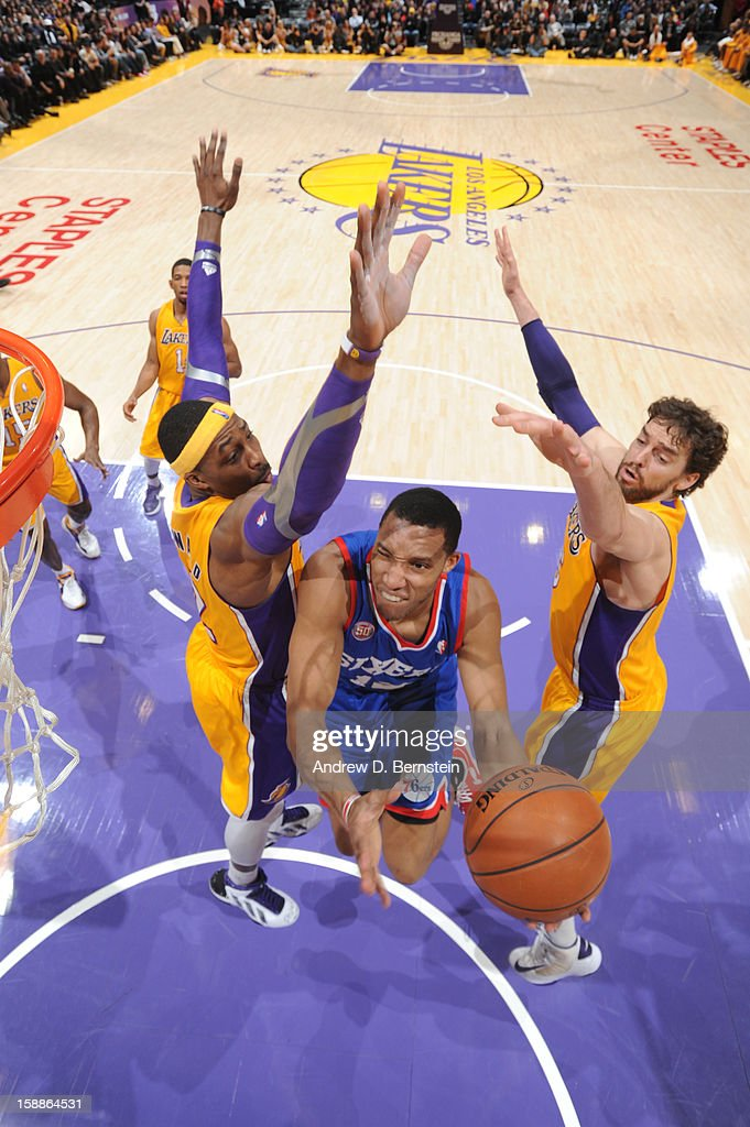 Evan Turner #12 of the Philadelphia 76ers goes to the hoop between Dwight Howard #12 and Pau Gasol #16 of the Los Angeles Lakers at Staples Center on January 1, 2013 in Los Angeles, California.