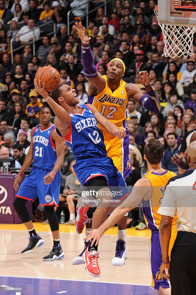 Evan Turner #12 of the Philadelphia 76ers goes up for a shot against Dwight Howard #12 of the Los Angeles Lakers at Staples Center on January 1, 2013 in Los Angeles, California.