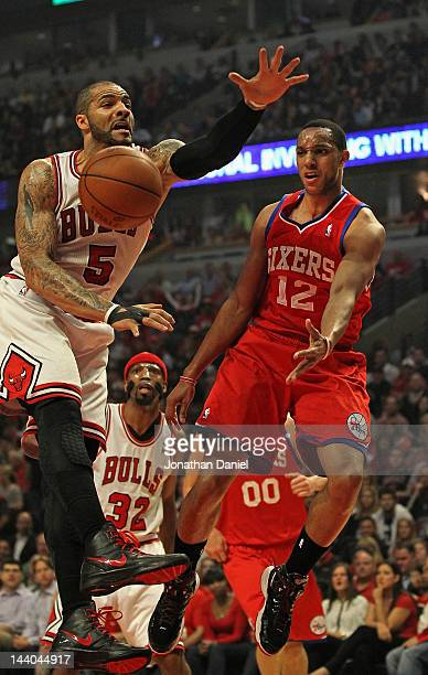 Evan Turner of the Philadelphia 76ers leaps to pass around Carlos Boozer of the Chicago Bulls in Game Five of the Eastern Conference Quarterfinals...