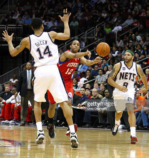 Evan Turner of the Philadelphia 76ers passes the ball as he is defended by Gerald Green and Deron Williams of the New Jersey Nets at Prudential...