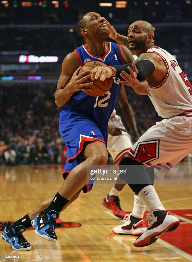 Evan Turner #12 of the Phildelphia 76ers is fouled by Carlos Boozer #5 of the Chicago Bulls at the United Center on February 28, 2013 in Chicago, Illinois.