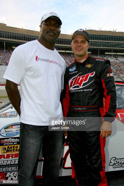 Evander Holyfield and David Gilliland driver of the moveforevercom/arthritisorg Dodge stand on the grid prior to the start of the NASCAR Nationwide...