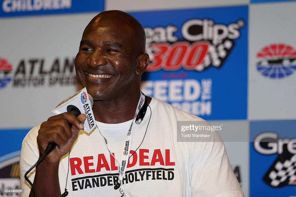 Evander Holyfield, boxing legend, speaks to the media prior to the NASCAR Nationwide Series Great Clips 300 at Atlanta Motor Speedway on August 30, 2014 in Hampton, Georgia.